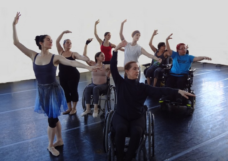 Infinity students, with instructor Kitty Lunn, perform a choreographic phrase together in a dance studio.