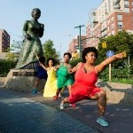 Four Black femmes in colorful dresses hold hands and form a line from a statue of Harriet Tubman pointing into the distance.