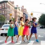 5 people in dresses, green, blue, yellow, pink, purple, stand in the crosswalk and look at the camera with NYC behind them.