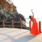 Dancer Yuritzi Govea in a flowing orange dress, by the ocean in Mexico, with her arm reaching to the waves and clouds