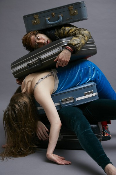 A photo of 3 people and suitcases piled on top of each other
