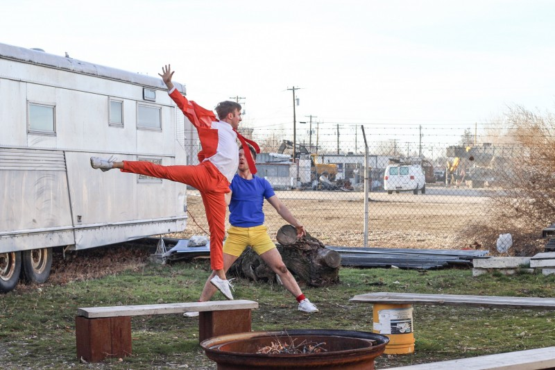 2 men in colorful clothing. One Jumping in the air; one standing with wide legs.