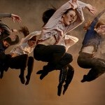 The members of the company leaping in the air in unison.