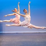 Two female dancers leap across the stage in pastel dresses