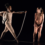 An African-American dancers stretches out a rope towards an Asian-American dancer