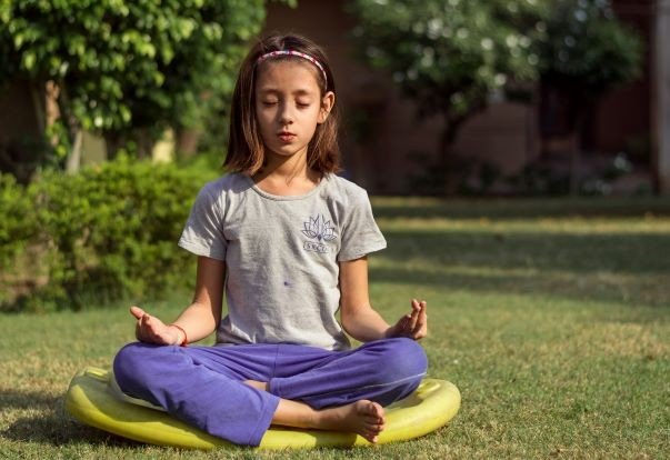 Child sitting outside in lotus pose meditating in blue pants