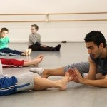 A Teaching Artist works with a young student on pointing his feet.