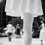 Black and white photo of a woman in a white skirt in the foreground standing on one leg, the other is missing.