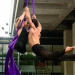 color photo of a muscular male and female aerialist spinning from purple silks, the female aerialist on the left has no legs