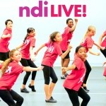 Children dancing in a studio. In bold bright purple letters it says ndiLIVE!