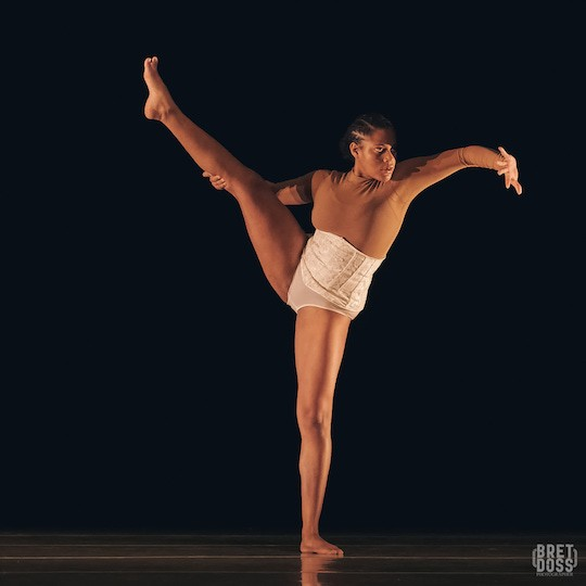 A single dancer stands facing the camera with her right leg lifted high to the side and her left arm pressing outward.