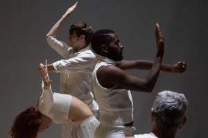 Dancers dressed in white face away from one another, holding one arm at a ninety-degree angle and the other flat.