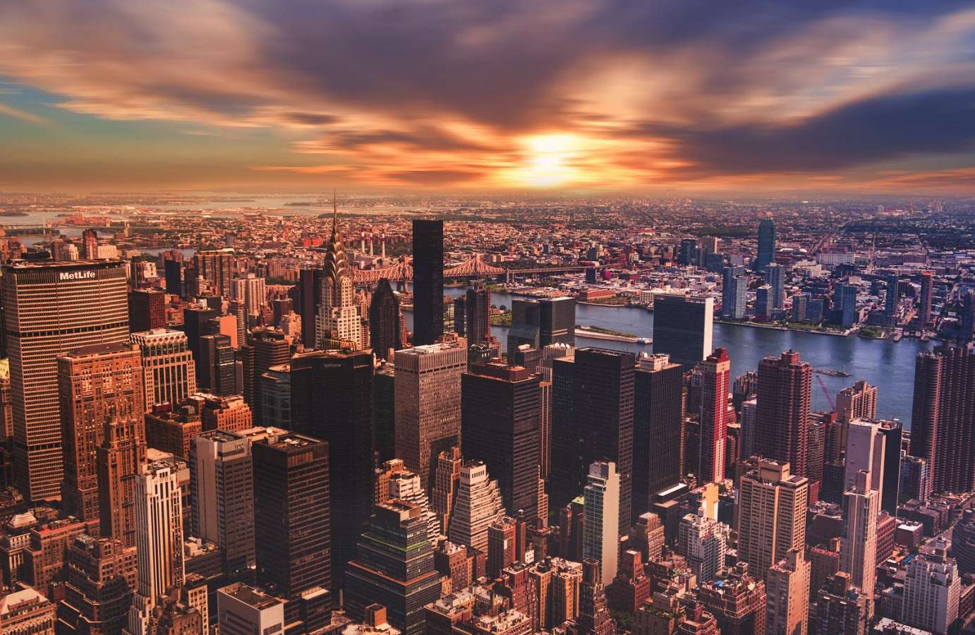 An image of the NYC skyline. The East River along with Brooklyn and Queens can be seen in in the background as the sun orange sun sets in the background, adorned with partly cloudy skies, creating a blue and orange melange of color.