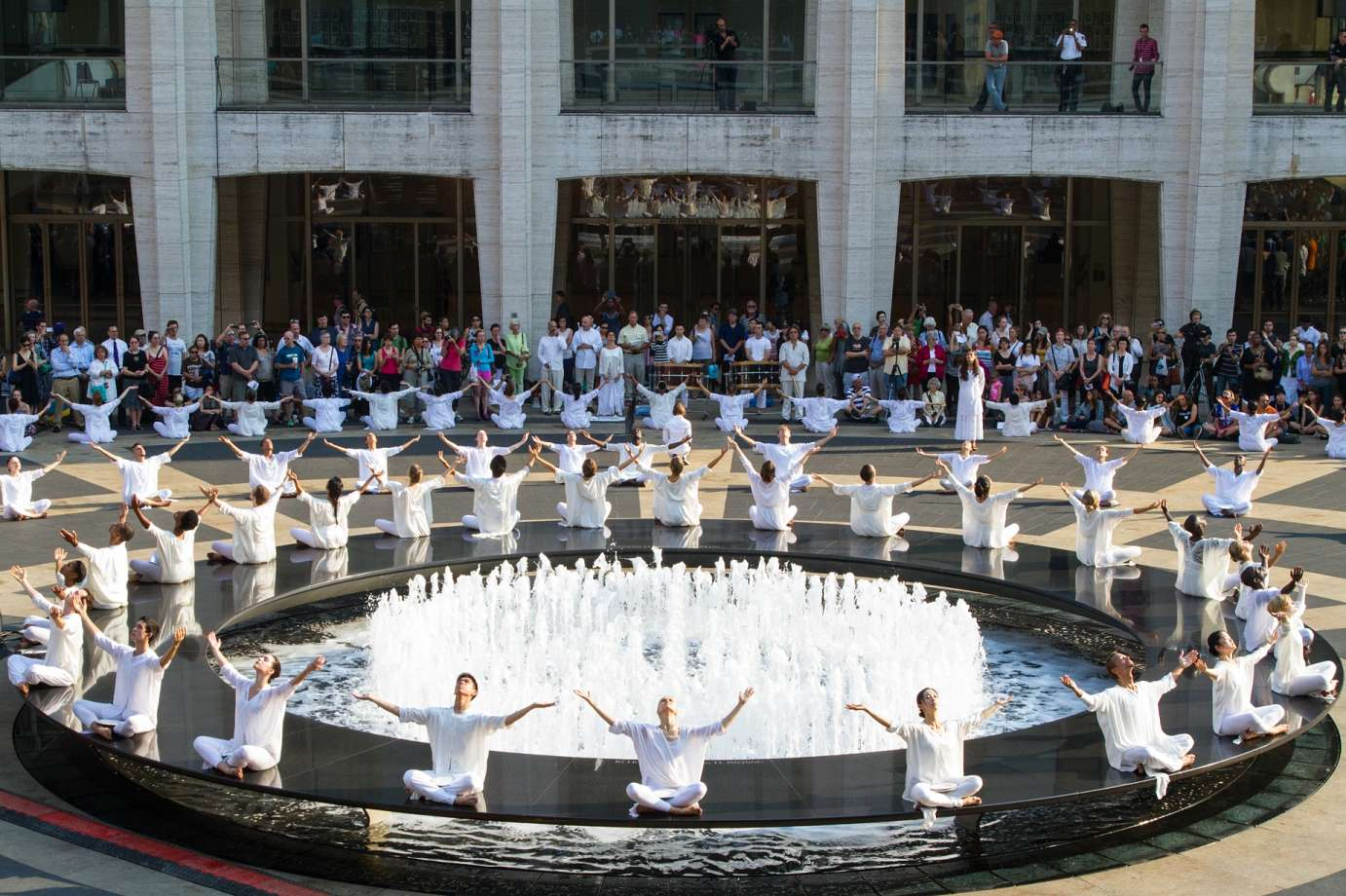 Dancers dressed in white surround Lincoln Center's Revron Fountain during the Table of Silence